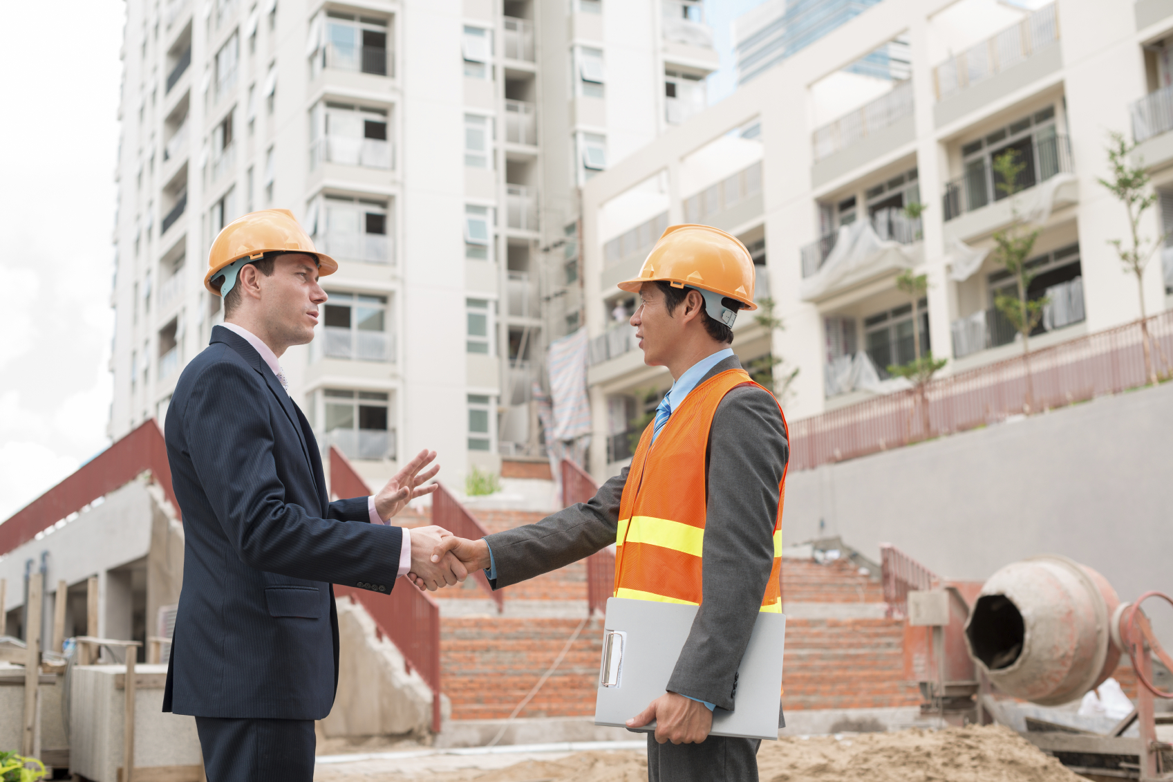 Businessman meeting Asian engineer at the construction site